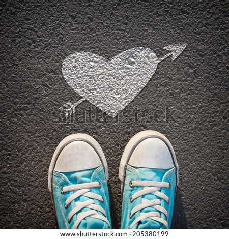 Male sneakers on the asphalt road with drawn heart - stock photo