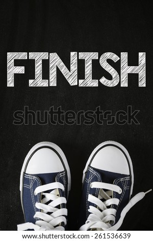 Male sneakers with finish word. Male sneakers with finish word on the back background - stock photo