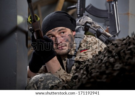 Male sniper in waiting position, hiding with sniper rifle - stock photo