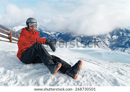 Male snowboarder against panoramic winter mountains background