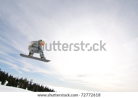 Male Snowboarder Catches Big Air on a Bright Sunny Day. - stock photo