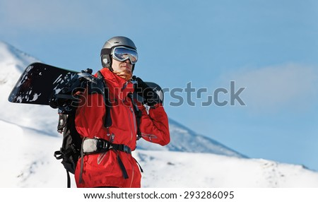 Male snowboarder holding a board with copy space - stock photo