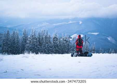 Male snowboarder looks into the distance on snowy mountain slopes