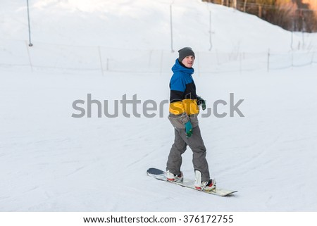 Male snowboarder walking in a winter day on the hill in the woods. Portrait of a snowboarder in the mountains in winter on the ski slope.
