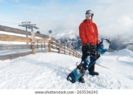 Male snowboarder with board against panoramic winter mountains background - stock photo