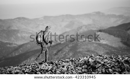 Male sportsman backpacker walking on the rocky mountain ridge with beautiful mountains on background. Man is wearing jacket and has trekking sticks and backpack on. Sunny day. black and white - stock photo