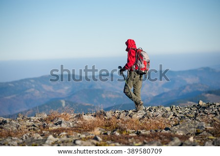 Male sportsman backpacker walking on the rocky top of the mountain with beautiful mountains on background. Man is wearing red jacket and has trekking sticks and backpack on. - stock photo