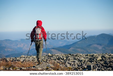 Male sportsman backpaker walking on the rocky top of the mountain with beautiful mountains on background. Man is wearing red jacket and has trekking sticks and backpack on. Rear view. - stock photo
