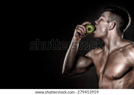 Male Sportsman Bites Green Apple After Training - stock photo