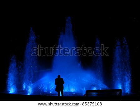 Male standing in front of a beautiful water feature fountain at night - stock photo