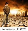 Male standing on cracked earth in front of a city - stock photo