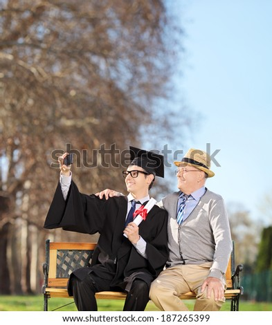 Male student and his proud father taking selfie in park shot with tilt and shift lens - stock photo