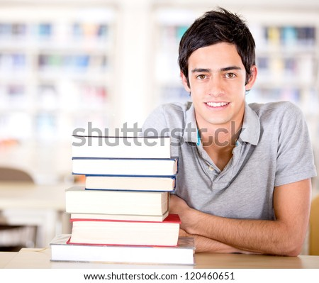 Male student at the library with a pile of books - stock photo