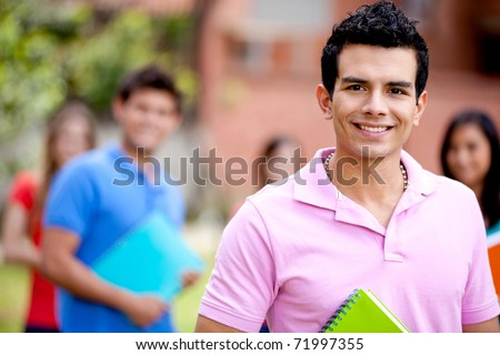 Male student carrying notebooks outdoors and smiling