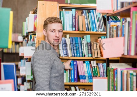 Male student chooses a book in the library