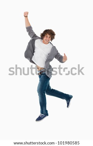 Male student dancing against white background