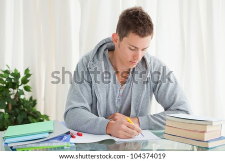 Male student doing his homework in his house - stock photo
