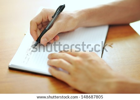 male student hand with a black pen writing on a white notebook
