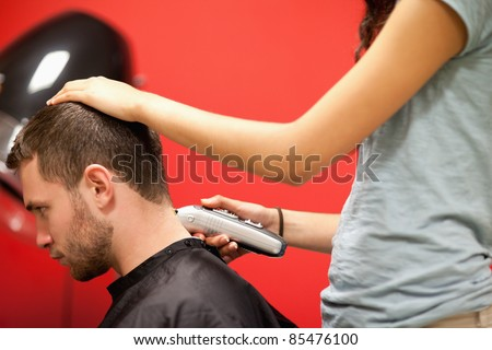 Male student having a haircut with a hair clippers - stock photo