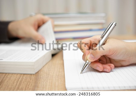 Male student is reading book, female is writing into notebook - stock photo
