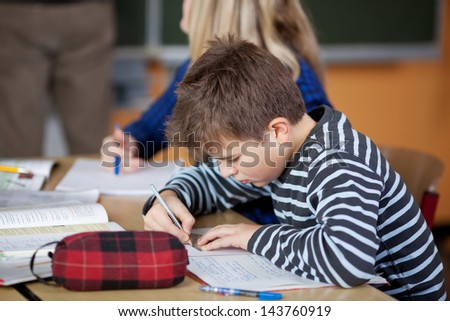 Male student is taking notes during class - stock photo