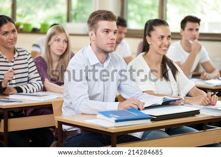 Male student listening  a lecture in classroom with colleagues - stock photo