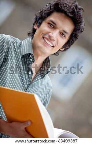 Male student outdoors holding a notebook and smiling