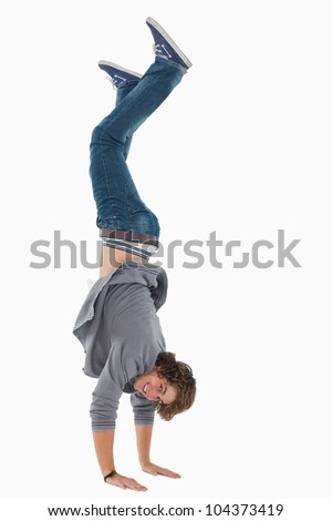 Male student posing handstands against white background - stock photo