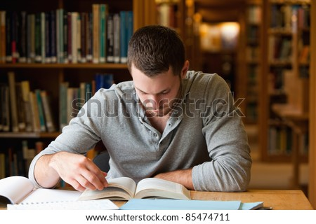 Male student researching with a book in a library - stock photo
