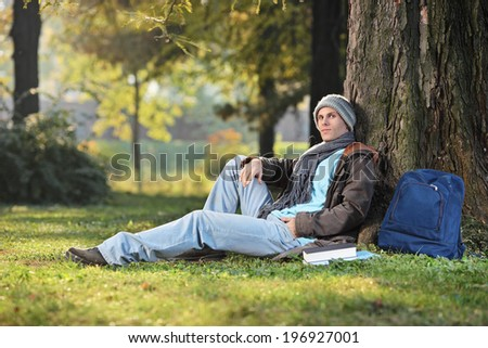 Male student sitting by a tree in park on a sunny day in autumn - stock photo