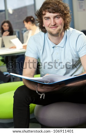 Male student sitting with folder at college with colleagues in the background - stock photo