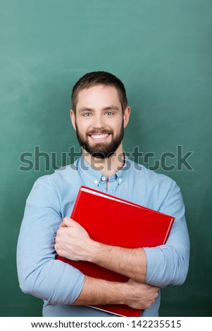 male student standing with red file in classroom - stock photo
