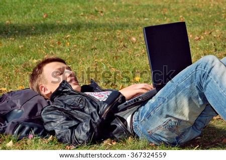 male student studying in park with laptop, youth lifestyle college - stock photo