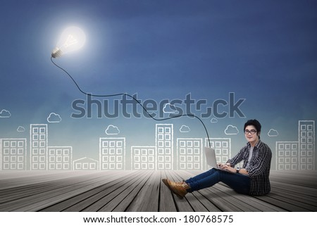 Male student studying with laptop outdoor - stock photo