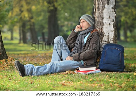 Male student thinking seated by a tree outdoors - stock photo