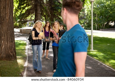 Male student waving to a group of female students - stock photo