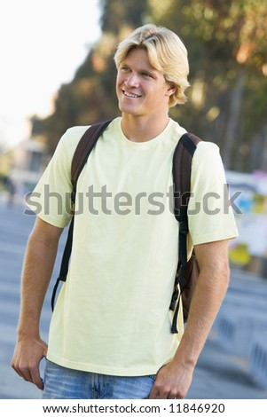 Male student wearing rucksack off campus - stock photo
