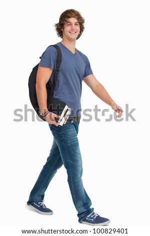 Male student with a backpack holding books while walking against white background