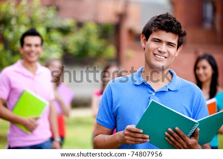 Male student with a notebook outdoors and smiling