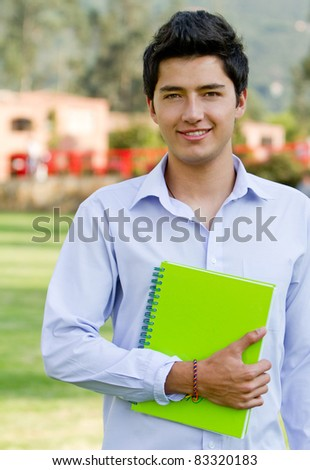 Male student with a notebook outdoors and smiling - stock photo