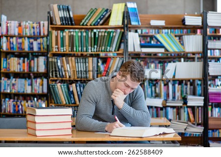 Male student with open book working in a library