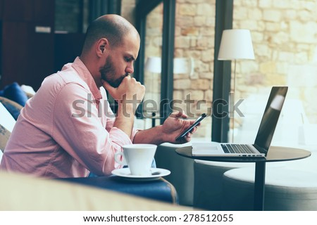Male student work on his computer while chatting on smart phone, young business man use laptop sitting at sofa of modern coffee shop or hotel hall, freelancer working on notebook at hipster loft space - stock photo