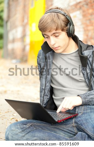 male student working on laptop, sitting near the wall - stock photo