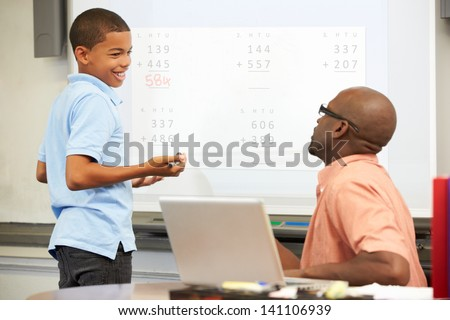 Male Student Writing Answer On Whiteboard - stock photo