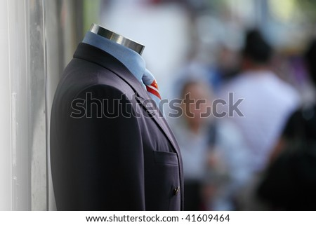 Male suit in street on display, people walking by. Shallow DOF. - stock photo