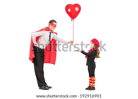 Male superhero giving a balloon to a little girl isolated on white background - stock photo