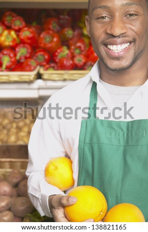 Male supermarket worker with fruits - stock photo