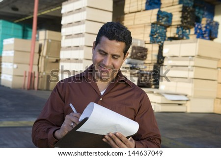 Male supervisor stock taking outside warehouse against stack of wood - stock photo