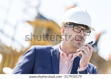 Male supervisor using walkie-talkie at construction site - stock photo