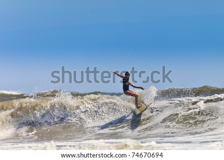 male surfer catching waves on the atlantic - stock photo